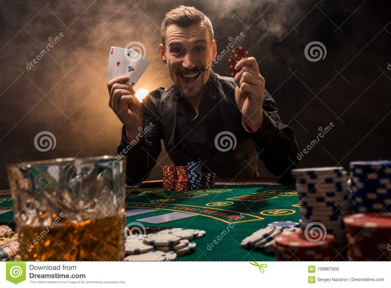 Handsome poker player with two aces in his hands and chips sitting at poker table in a dark room full of cigarette smoke