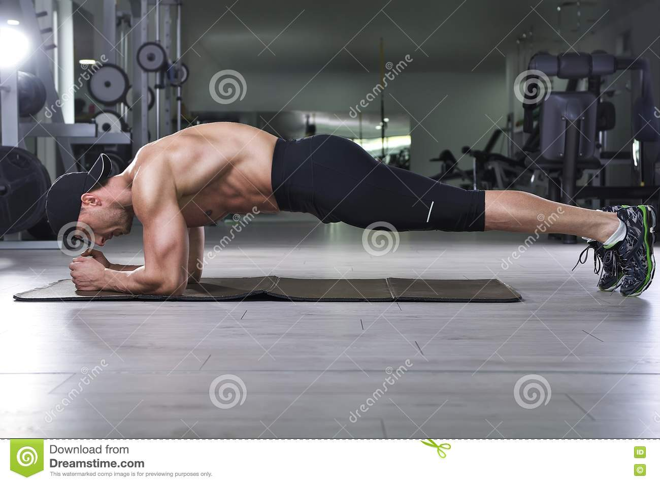 Handsome powerful athletic man doing plank exercise.