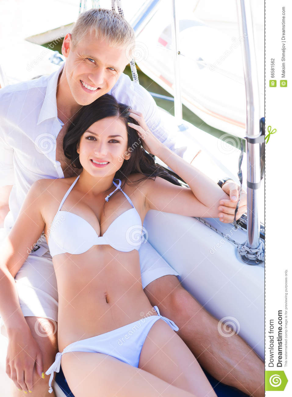 f8b05a1ab3 Handsome and rich men and a beautiful and women in a swimsuit relaxing on a sailing  boat