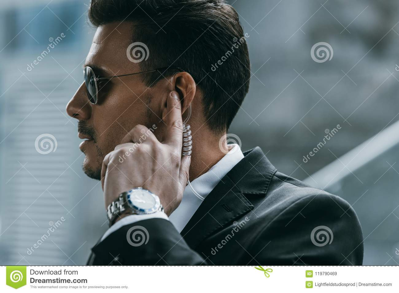 handsome security guard standing and listening message with security