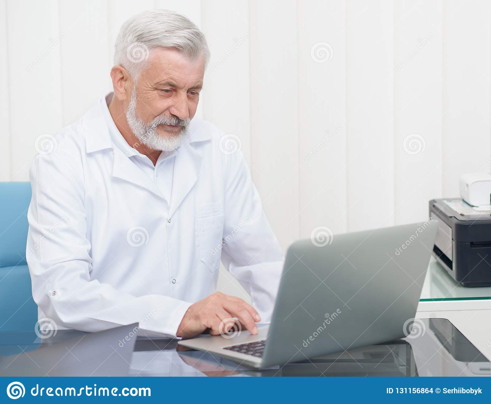 Senior doctor wearing in white uniform working with laptop.