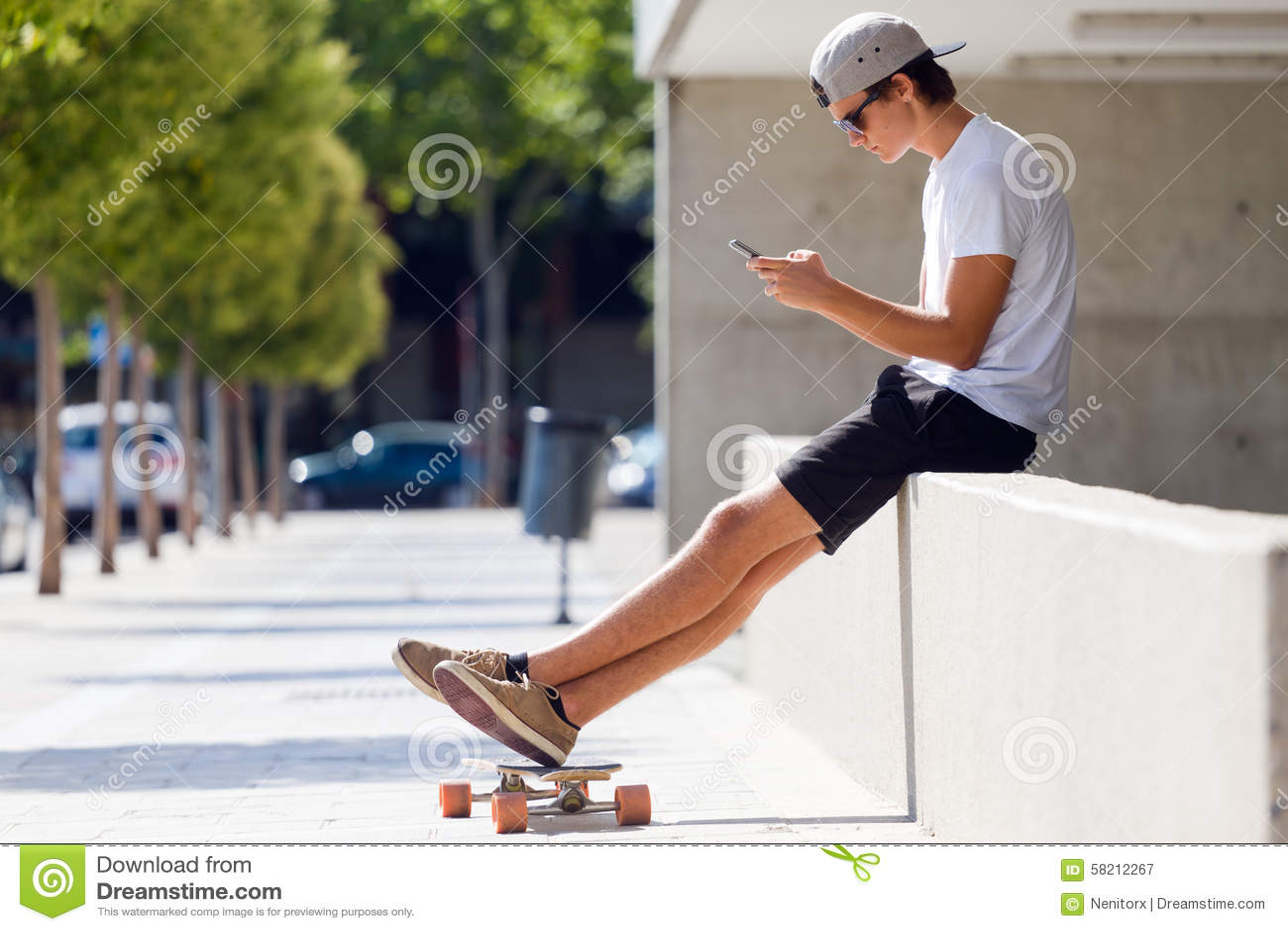 Handsome skater boy using his mobile phone in the street - Skateboard mobel ...
