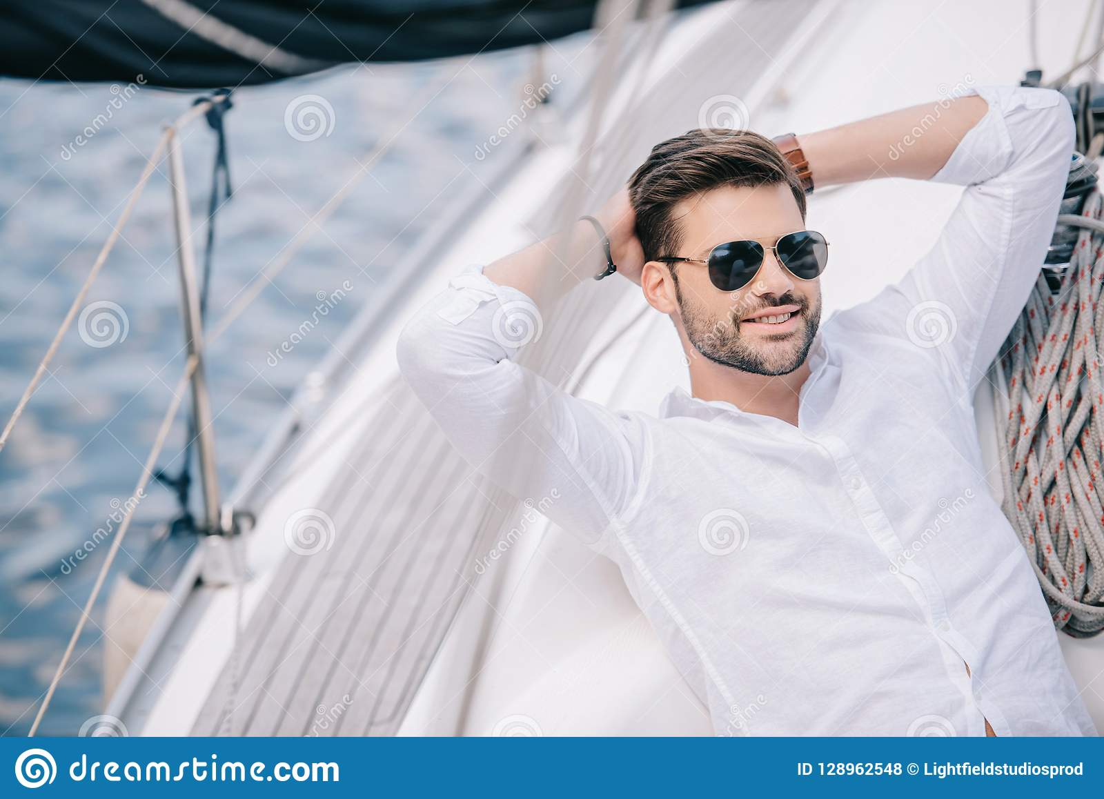 handsome smiling young man in sunglasses resting with hands behind head