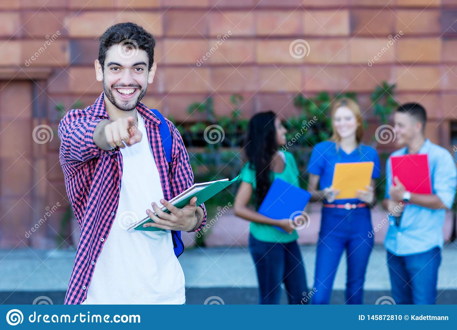 Handsome spanish male student with group of students. Outdoor in the summer in the city stock photo