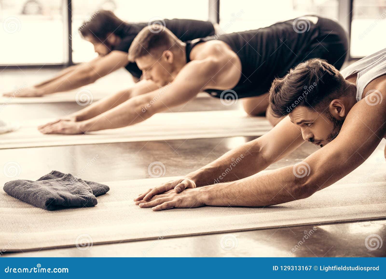 handsome sportsmen simultaneously stretching backs
