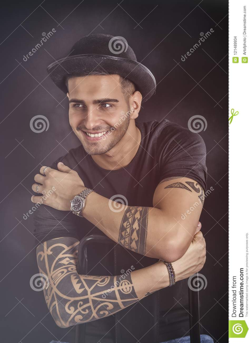 04086067e99 Handsome and stylish young man with black bowler hat and t-shirt. Cool  tattoos on arms