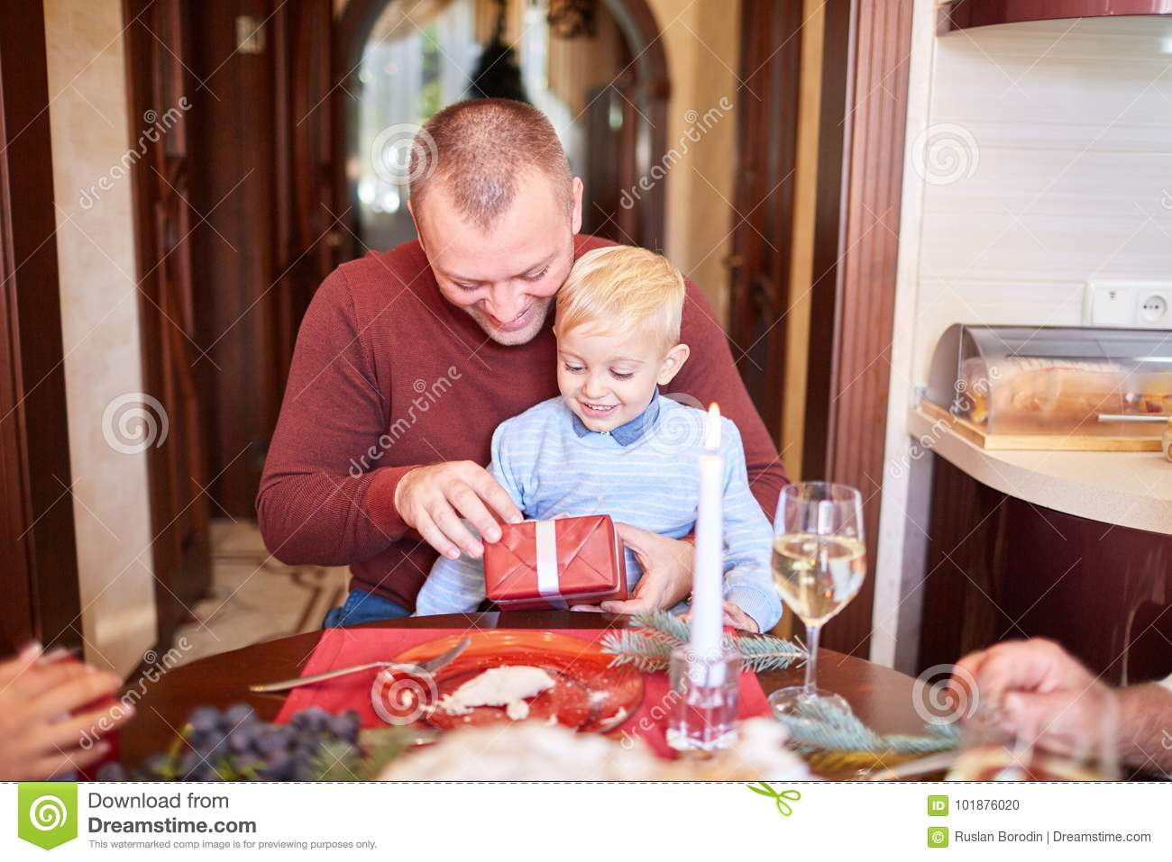 Dad giving a red gift to little son on a festive background. Family Christmas presents concept.