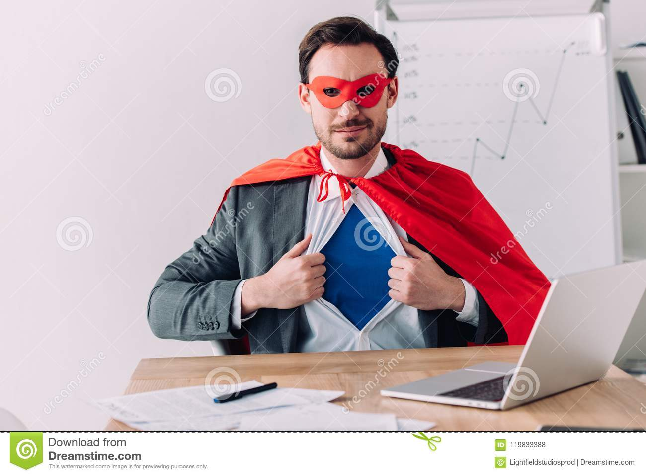 handsome super businessman in mask and cape showing blue shirt
