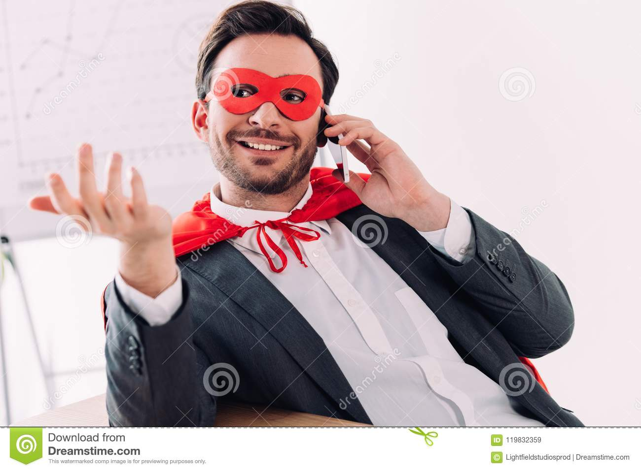 handsome super businessman in mask and cape talking by smartphone
