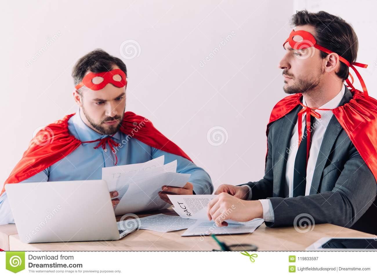 handsome super businessmen in masks and capes working with documents
