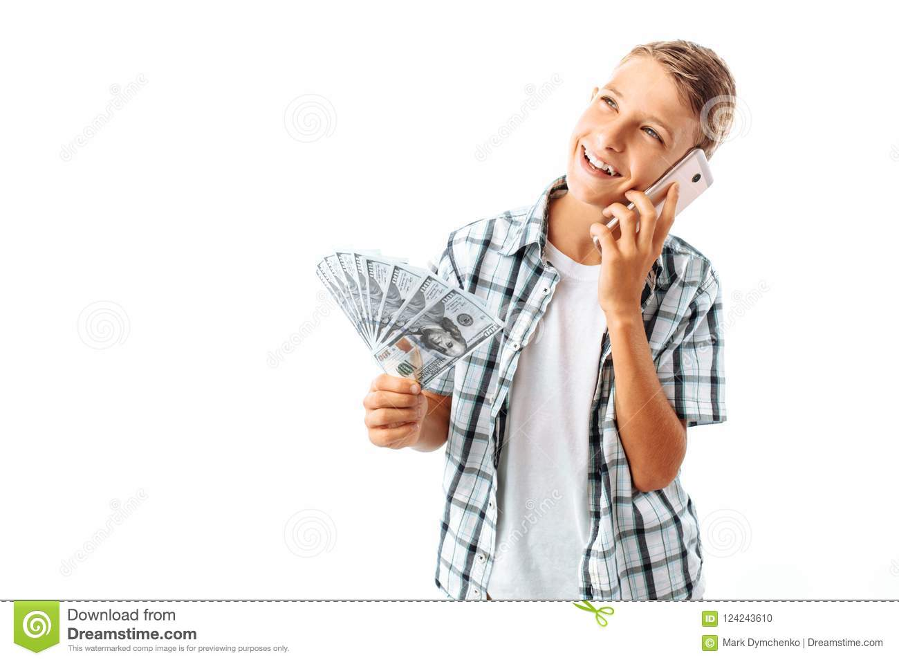 Handsome Teen guy with money in his hands, talking on the phone, joyful man holding dollars, in Studio on white background