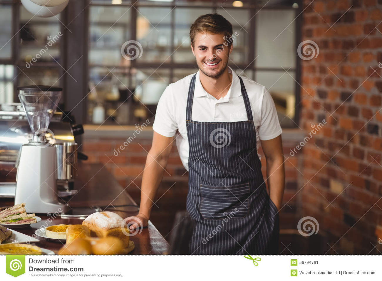 Handsome Waiter Leaning On A Food Table Stock Photo