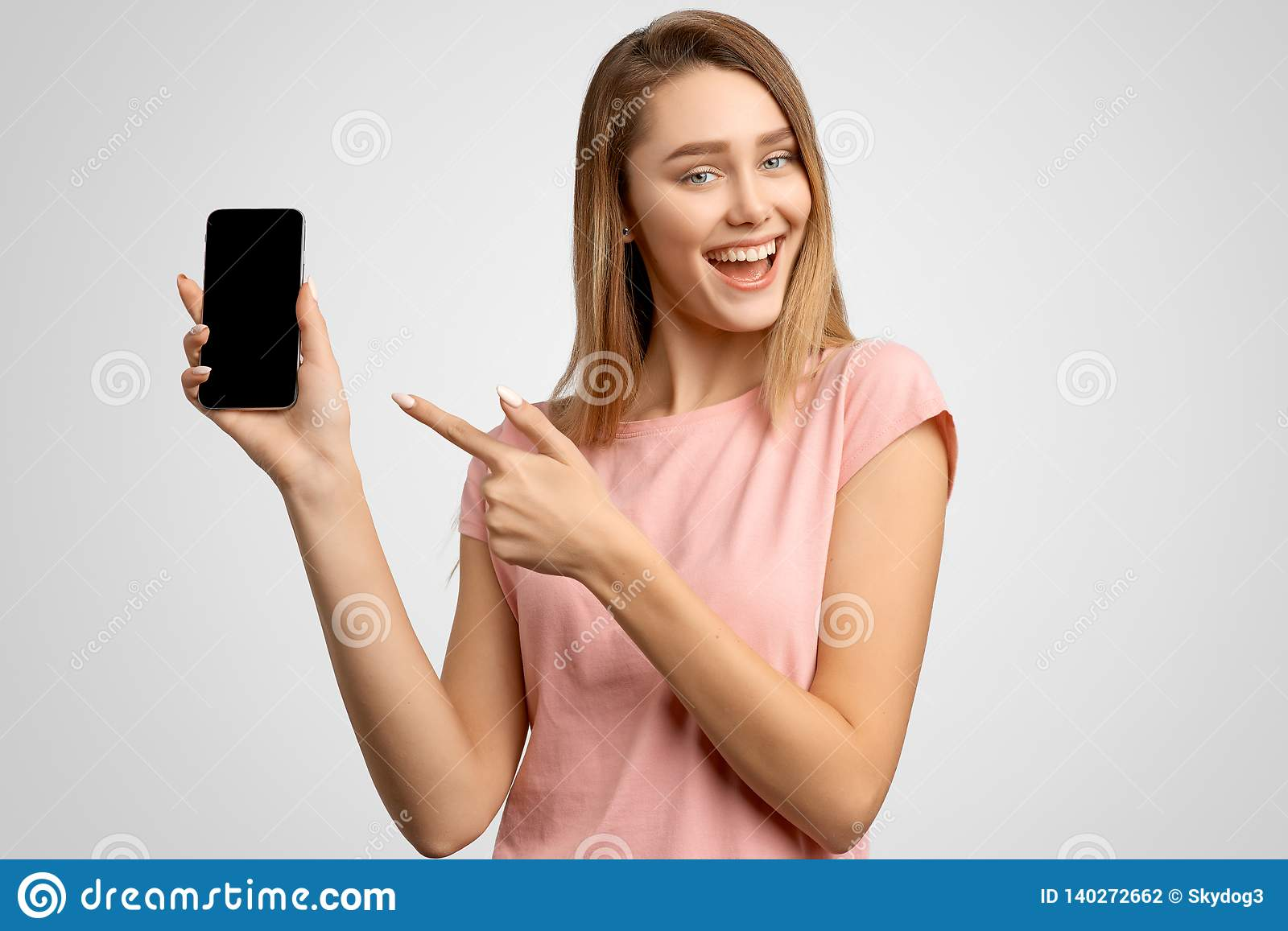 Handsome Woman With Index Finger Shows Blank Phone Screen Where You Can Place Your Ad Positive Young Girl Smiles Snow White Smile Stock Photo Image Of Digital Business 140272662