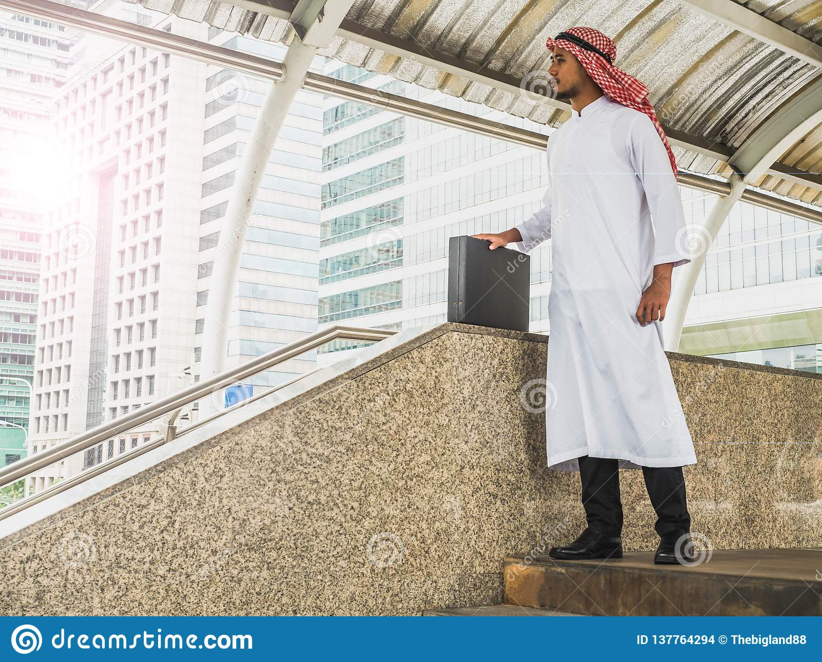 Handsome young arabic male, Middle east business man standing outdoor while looking for some direction