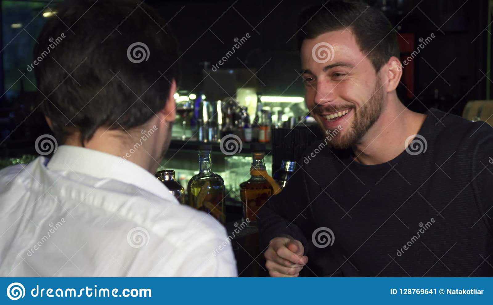 Young male friends talking while having drinks together at the bar