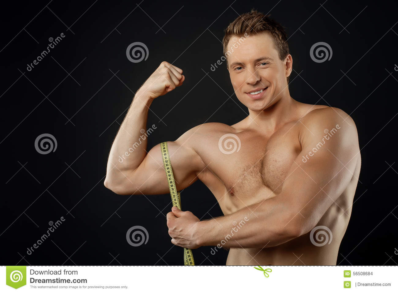 Handsome Young Bodybuilder Is Measuring His Stock Photo - Image of