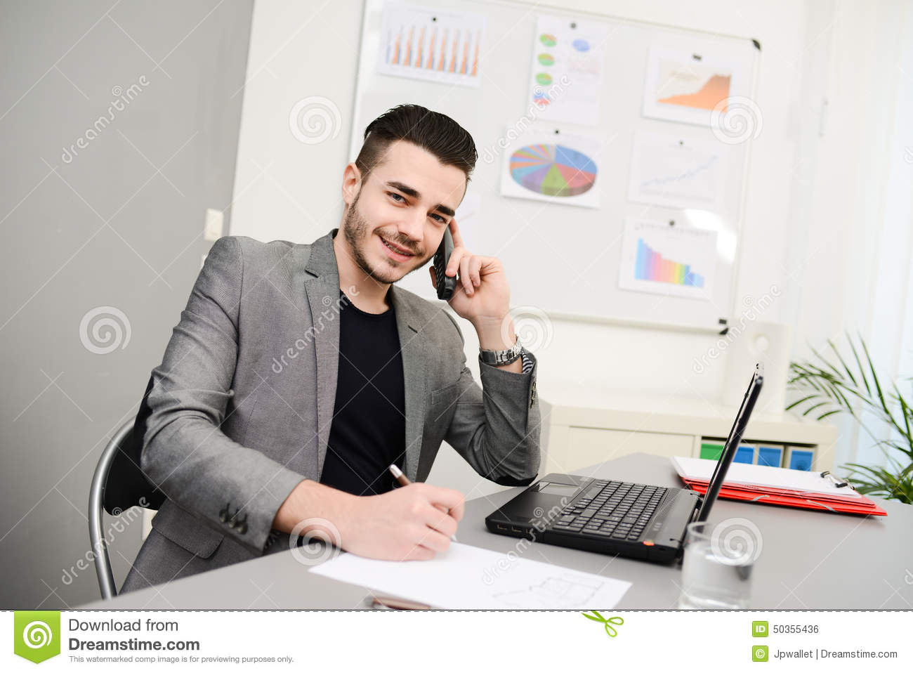 handsome-young-business-man-working-office-casual-cothes-laptop-computer-phone-50355436.jpg