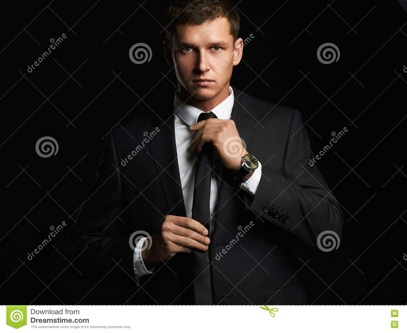 Handsome young businessman adjusting his tie. young man in suit