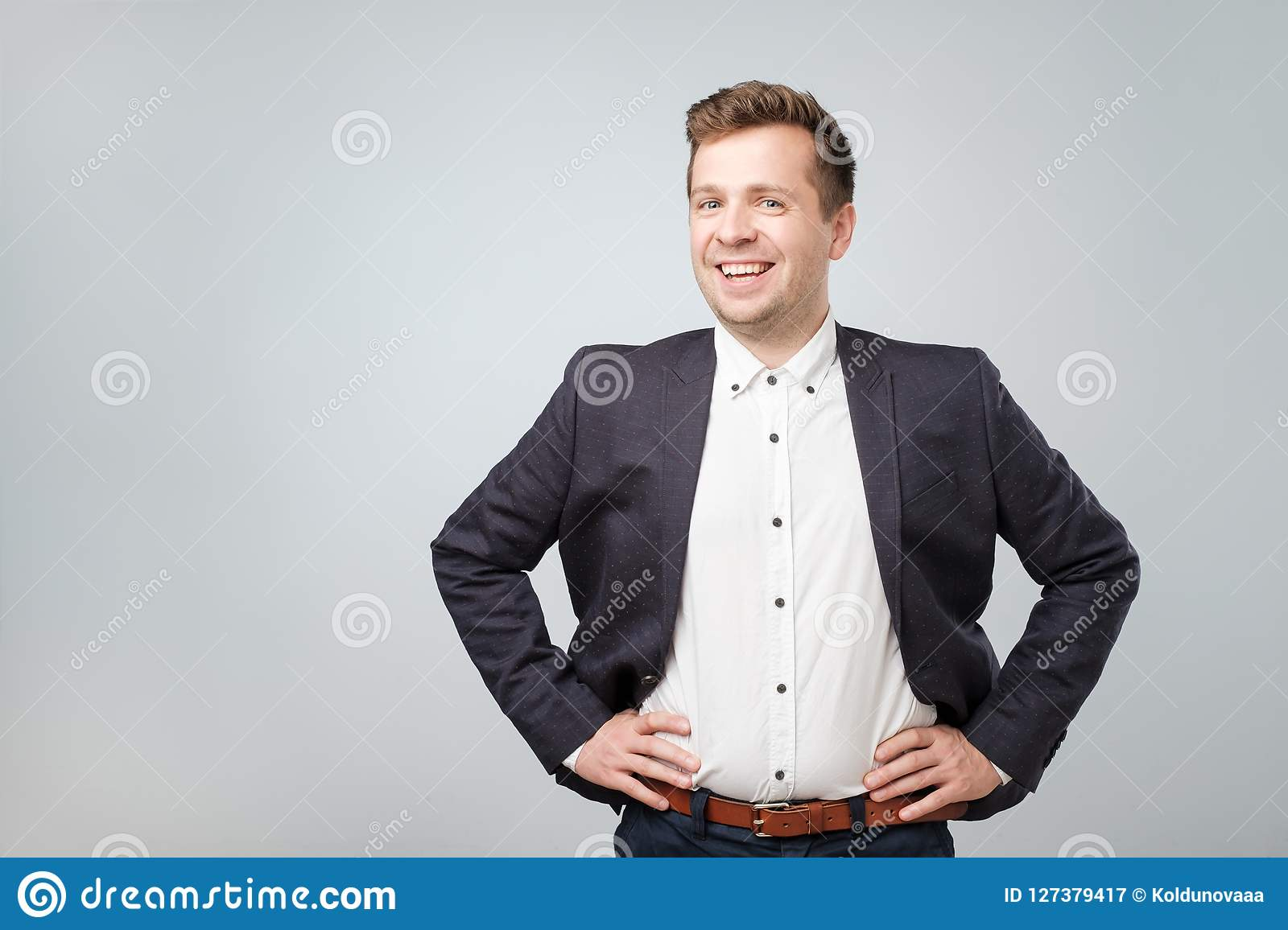 Handsome young caucasian businessman looking at camera.