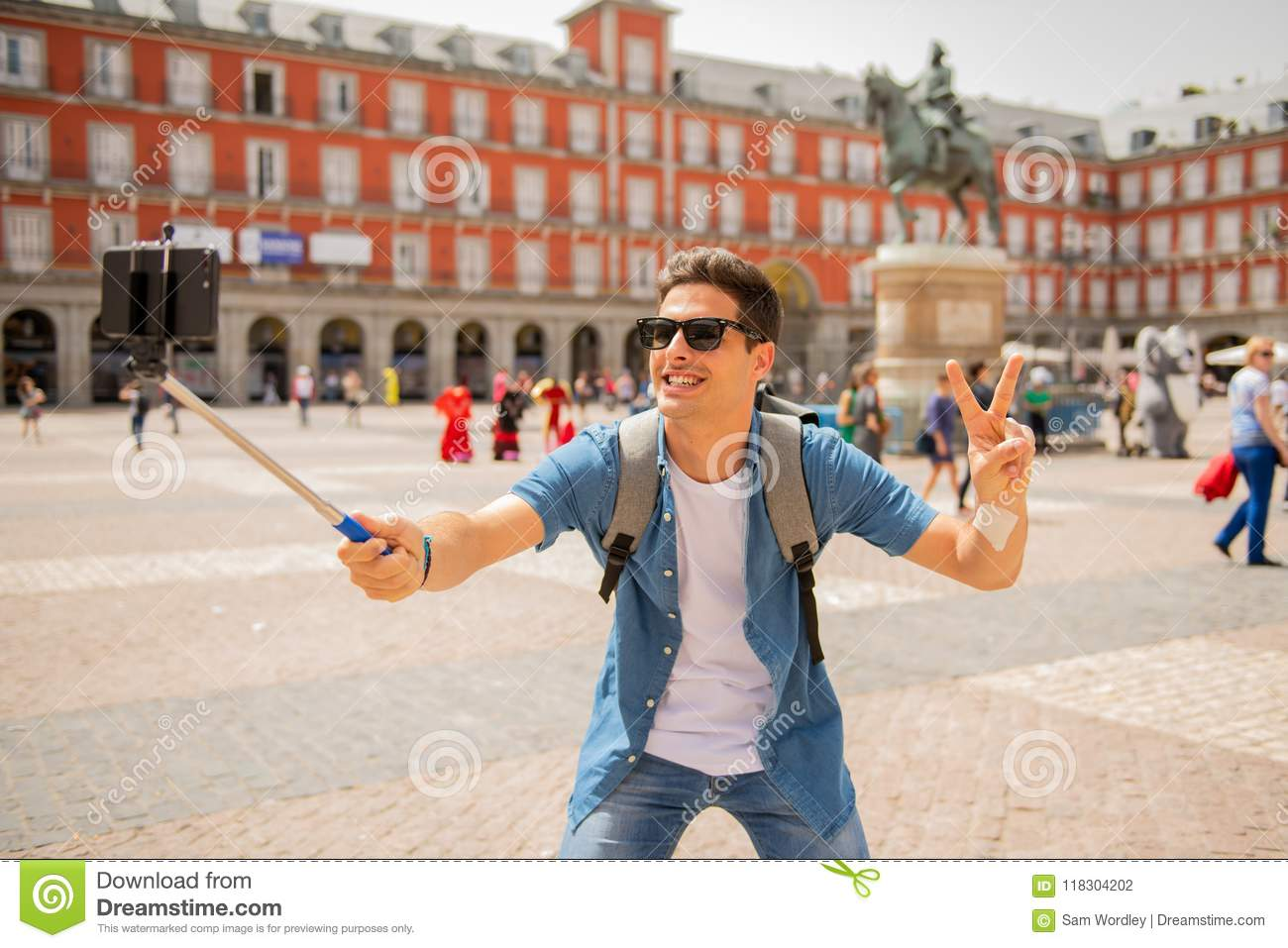 Handsome young caucasian tourist man happy and excited taking a selfie in Plaza Mayor, Madrid Spain