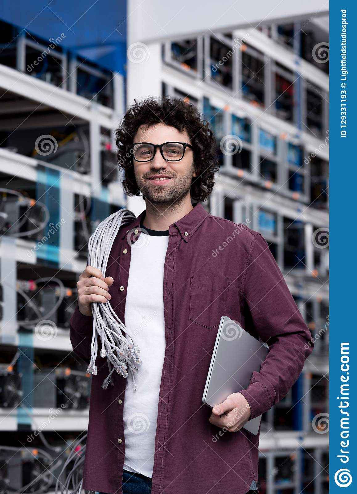 Handsome young computer engineer with laptop and wires working at cryptocurrency mining farm stock photos