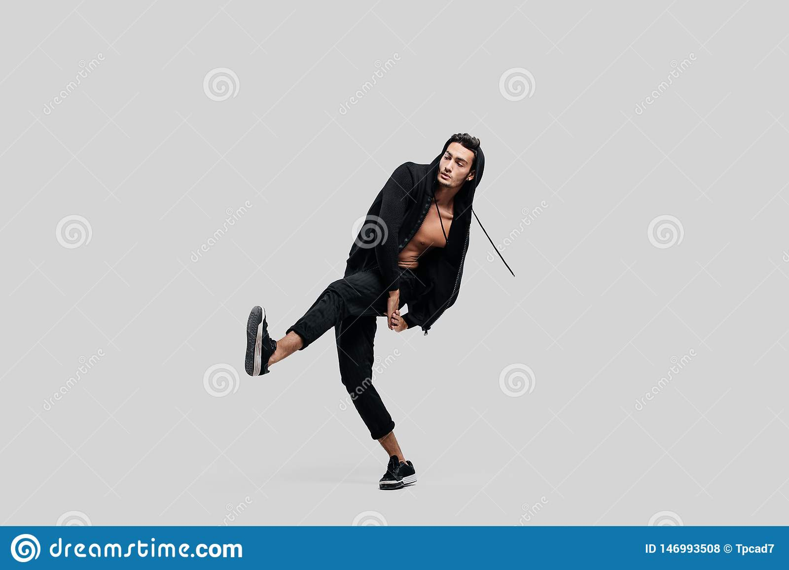 Handsome young dancer dressed in black pants, a sweatshirt on a naked torso lifts one leg up while dancing street dance