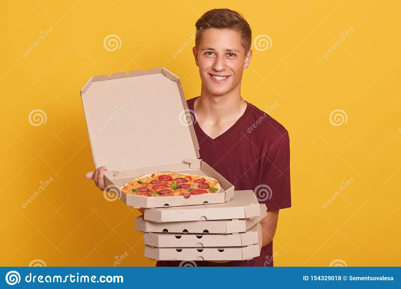 Handsome young delivery worker holding stack of pizza boxes, dressed casual t shirt, looking at camera and smiling, showing open