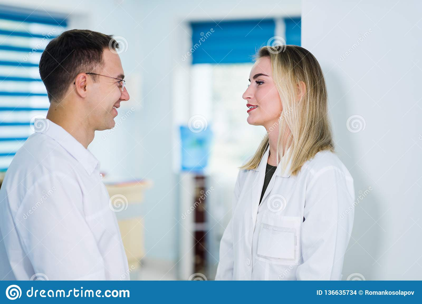 Handsome young doctor is talking with his beautiful female assistant, standing in waiting room of the clinic