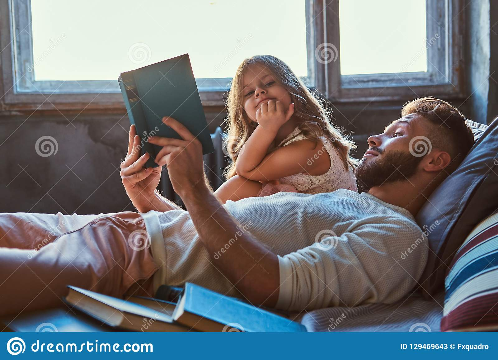 Handsome young father reading storybook his little daughter on bed.