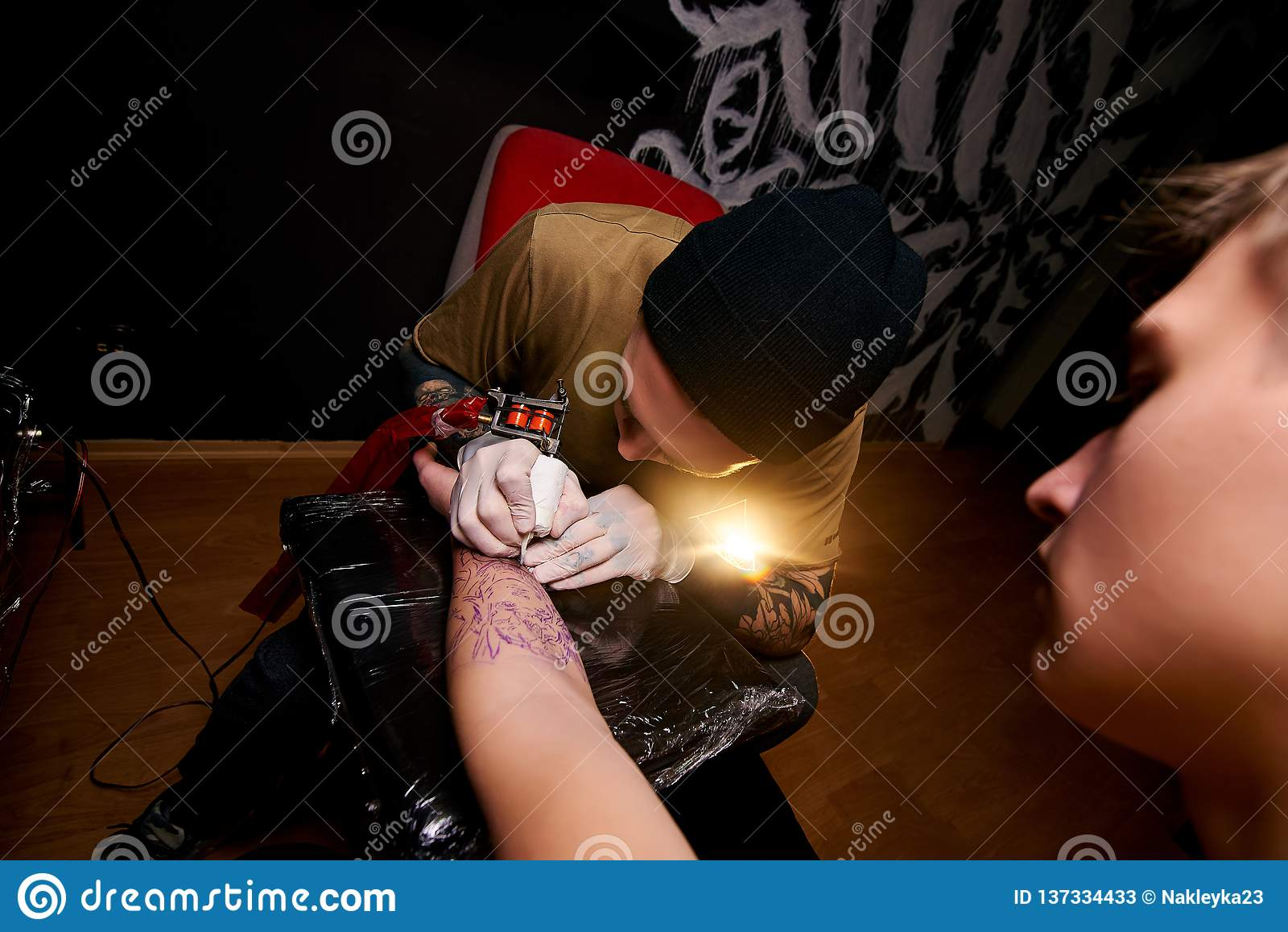 Handsome young guy in a black hat and with tattoos, beats a tattoo on his arm, tattoo salon