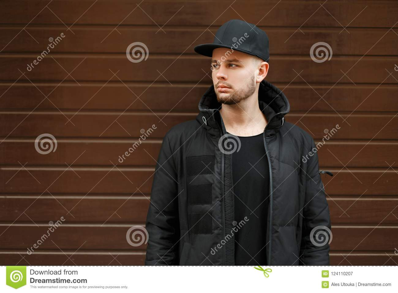 0261ccd0538 Handsome young hipster man in a black stylish baseball cap and winter  jacket stands near the wall