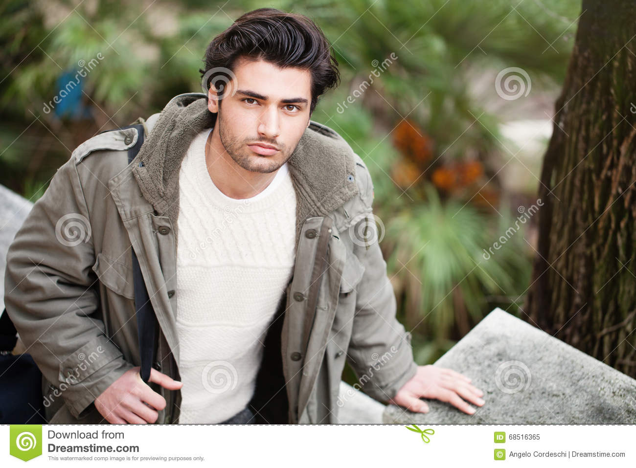 Handsome young italian man, stylish hair and coat outdoors