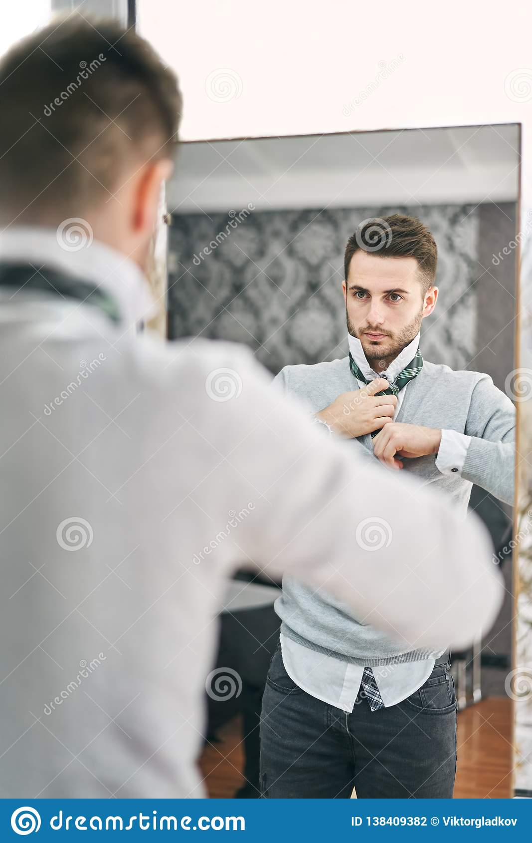 Handsome young man adjusting a tie in front of the mirror
