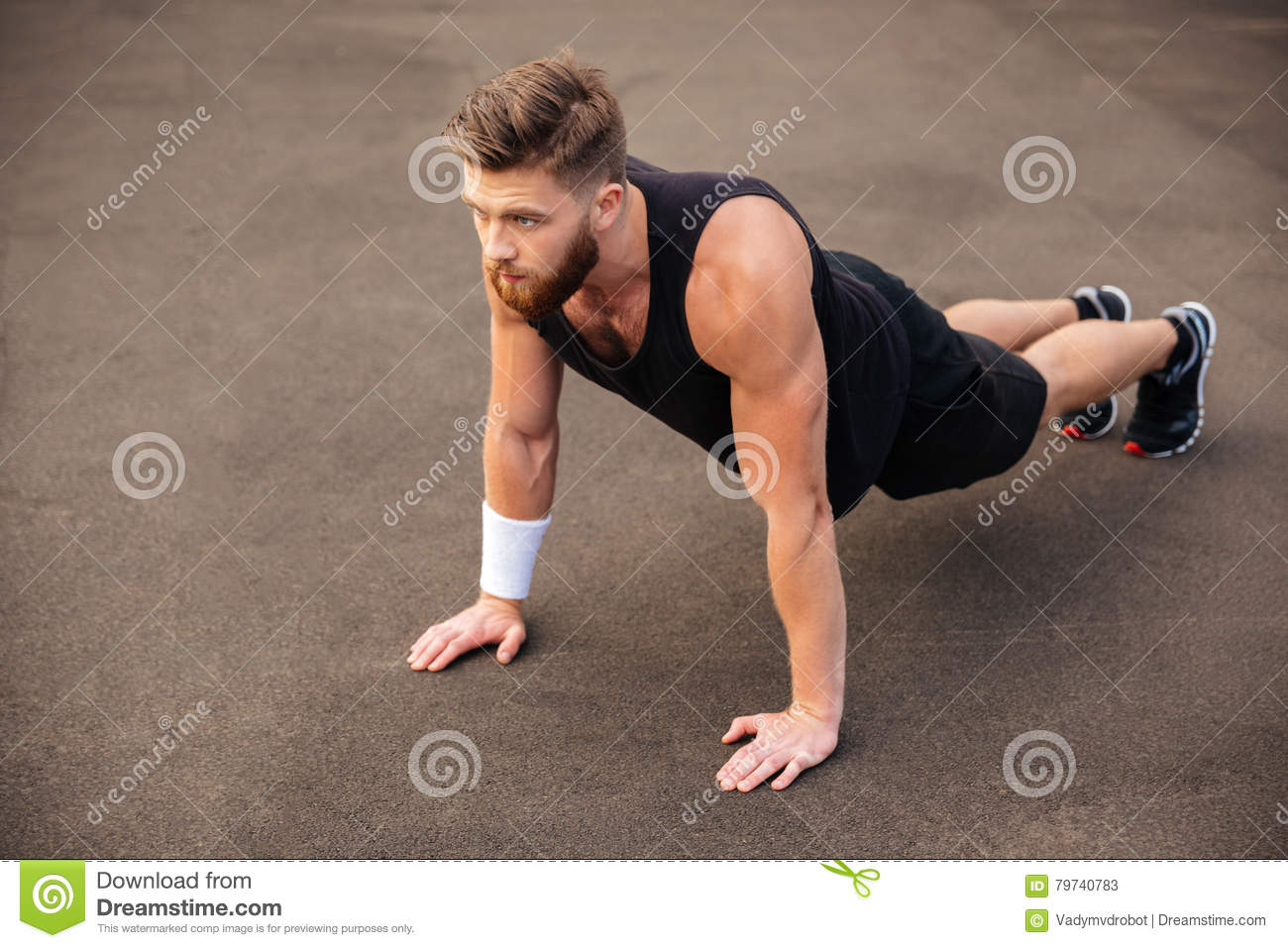 Handsome young man athlete training and doing plank exercise outdoors