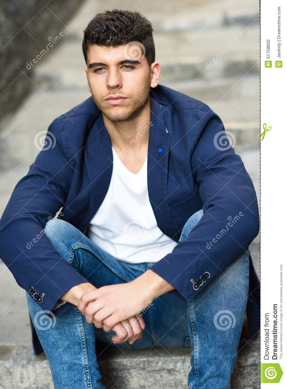 Handsome young man with blue eyes posing near a wall  Good Looking Young Man