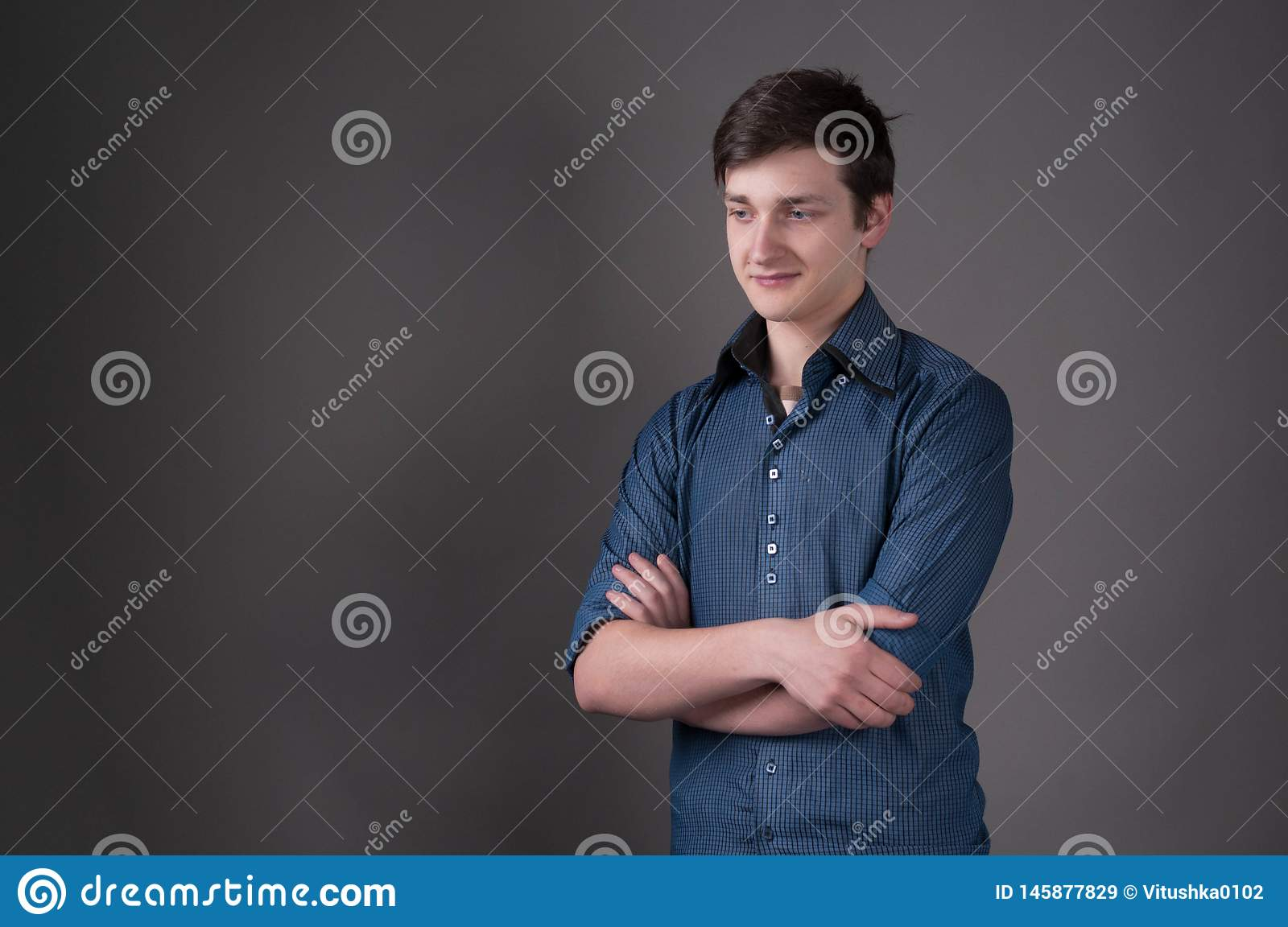 Handsome young man in blue shirt looking away with crossed arms and on grey background