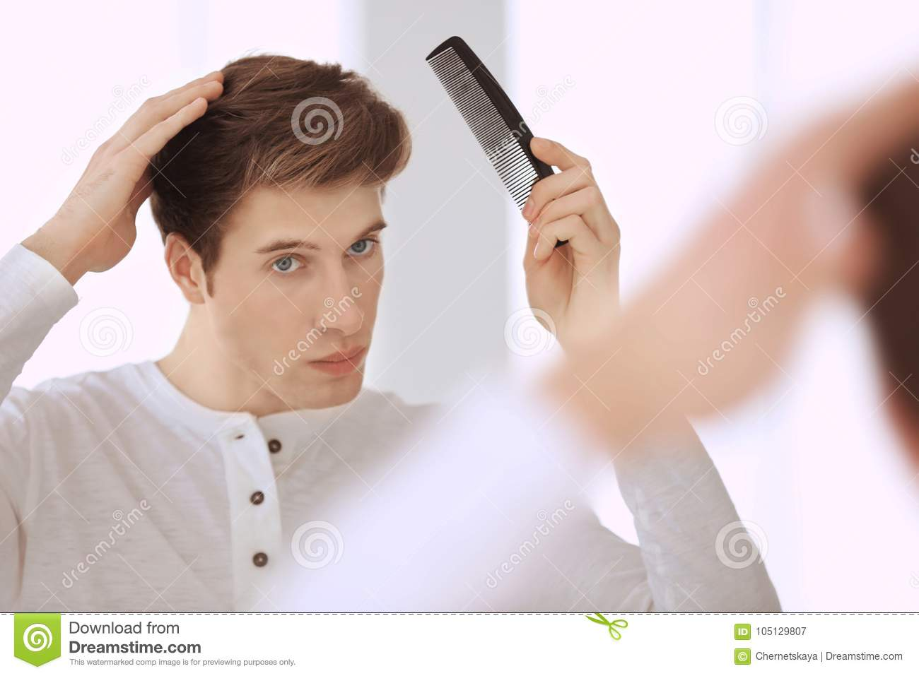 Handsome Young Man Combing Hair While Standing Stock Image