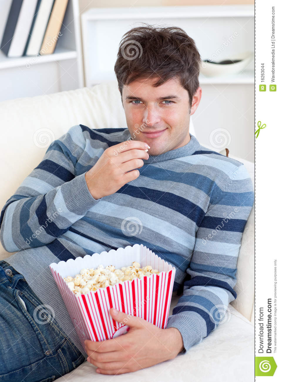 handsome-young-man-eating-popcorn-lying-