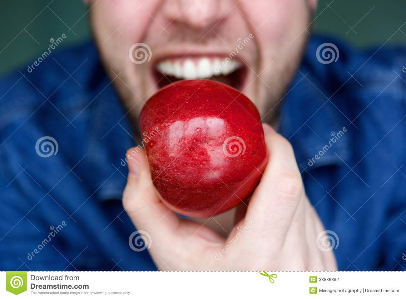 Handsome young man eating red apple