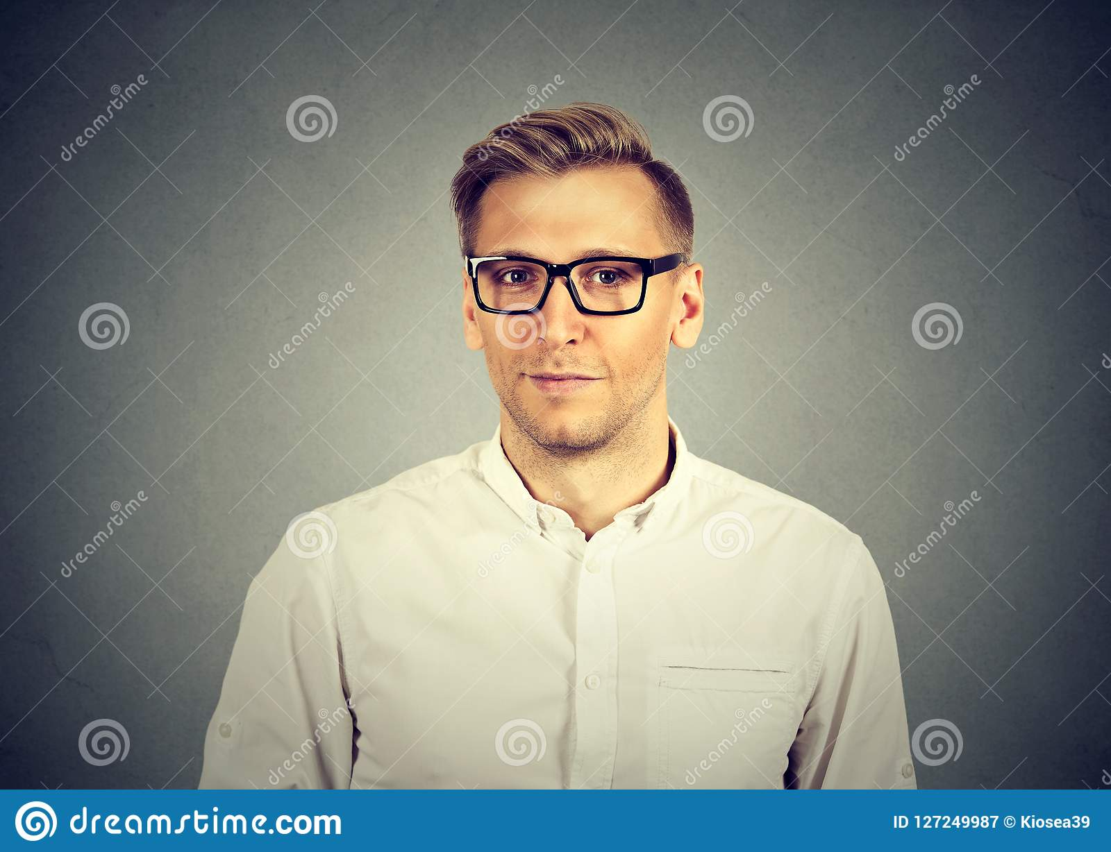 b1df5bbe0cd Adult handsome man in white shirt and black eyeglasses looking at camera on  gray background