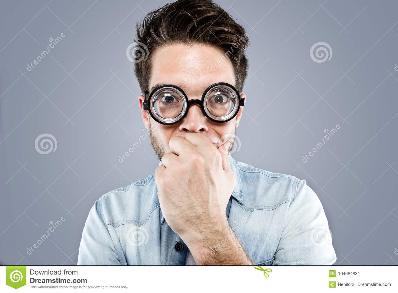 Handsome young man with funny glasses joking and making funny face over gray background.