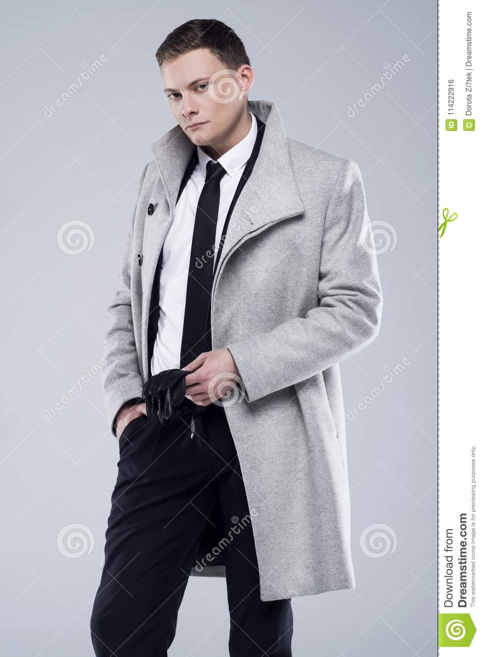 Handsome young man in a gray coat and black suit