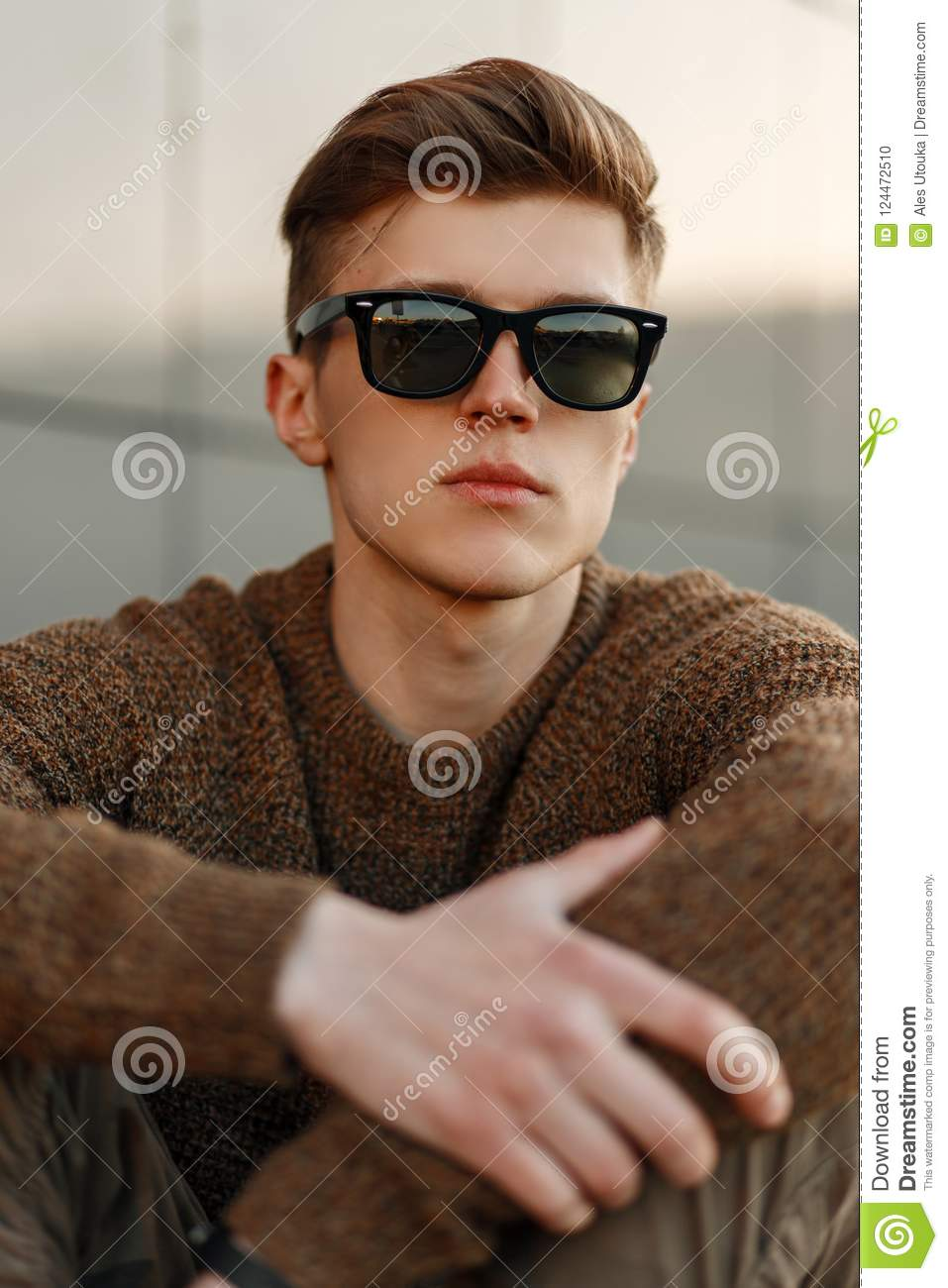 4e1f75f0512 Handsome young man hipster with sunglasses with hairdo in pullover on the  street