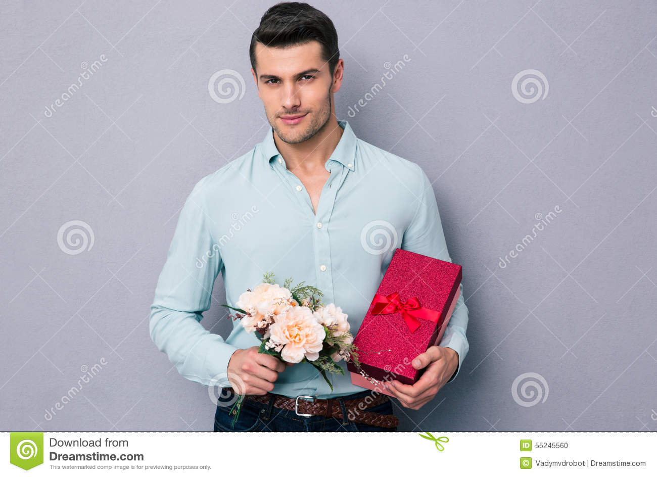 Gifts For Young Men: Handsome Young Man Holding Gift Box And Flowers Stock