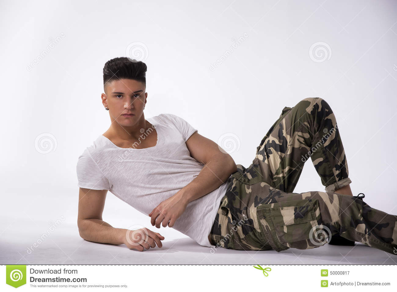 handsome young man laying down on floor white background stock