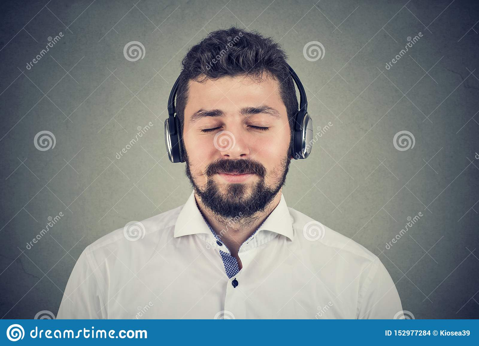 Handsome young man listening to music wearing headphones