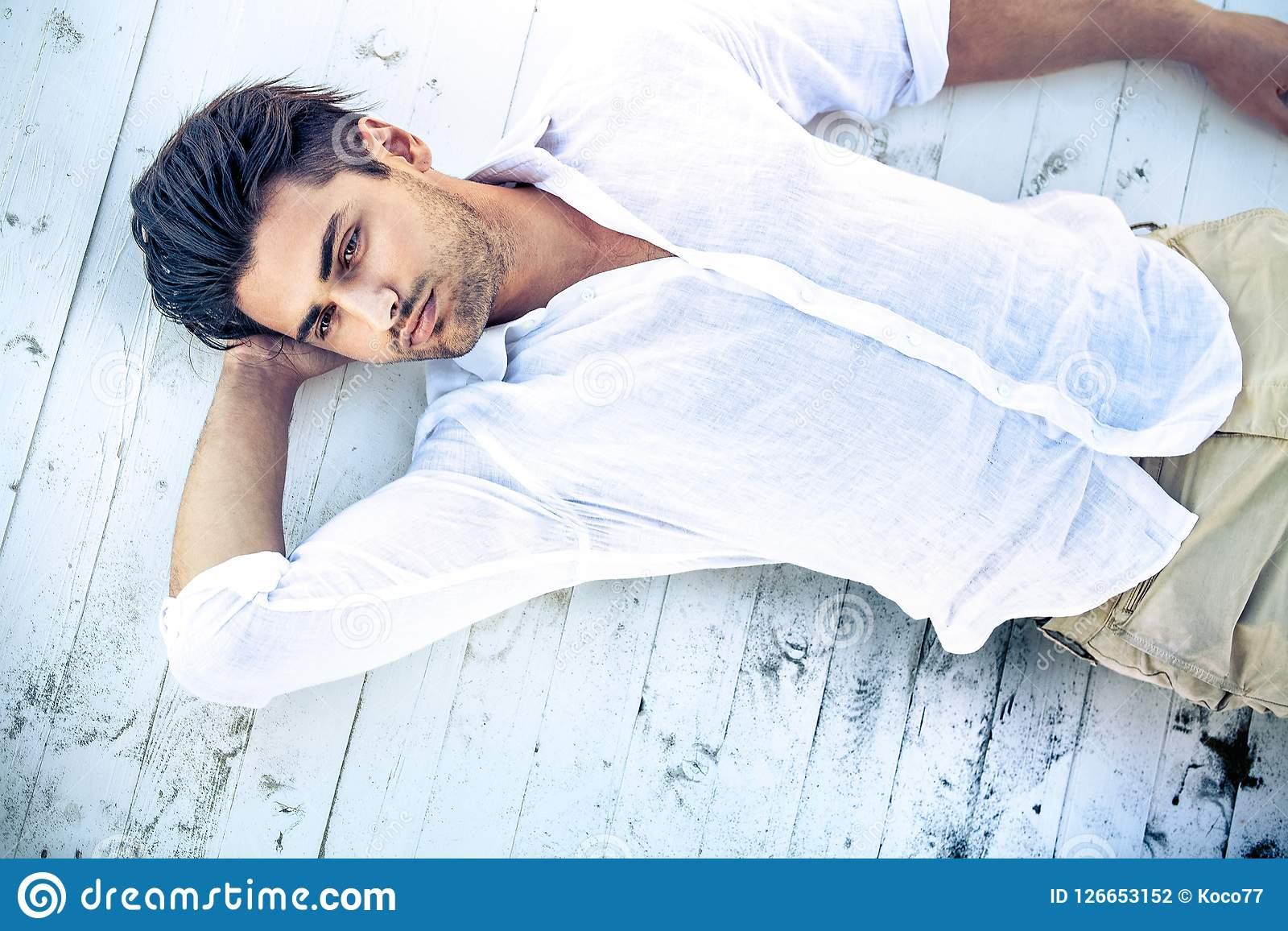 Handsome young man lying on a white wooden surface.