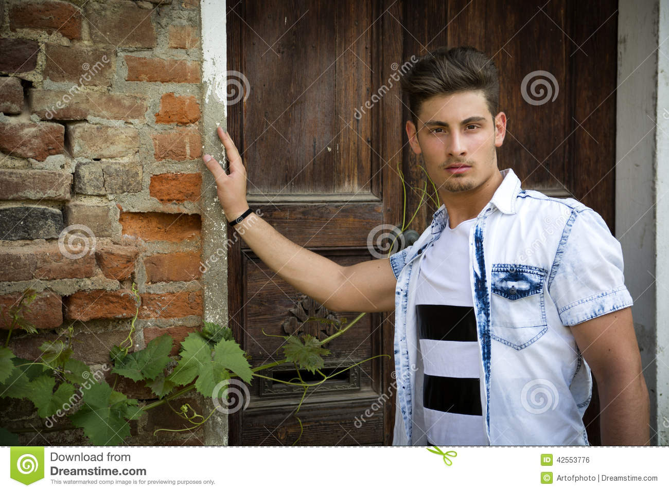 Handsome young man outdoors in front of old house