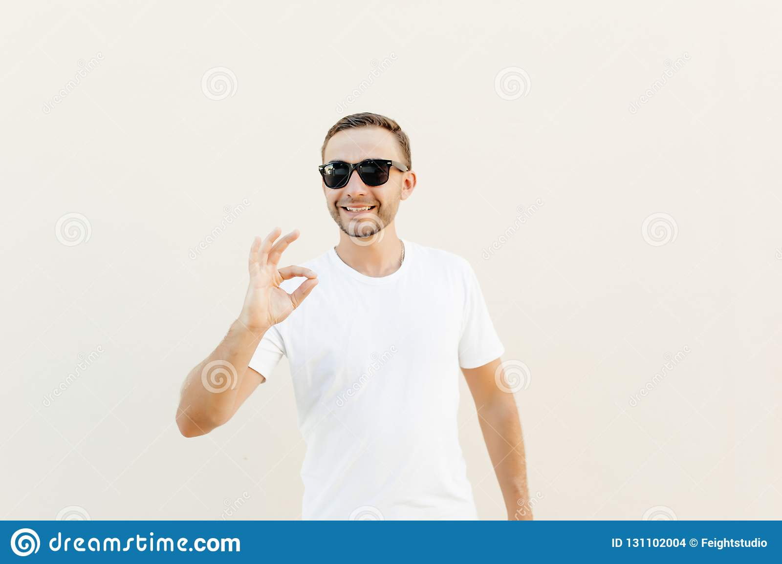 Handsome young man over orange wall wearing sunglasses doing happy thumbs up gesture with hand. Approving expression looking at th