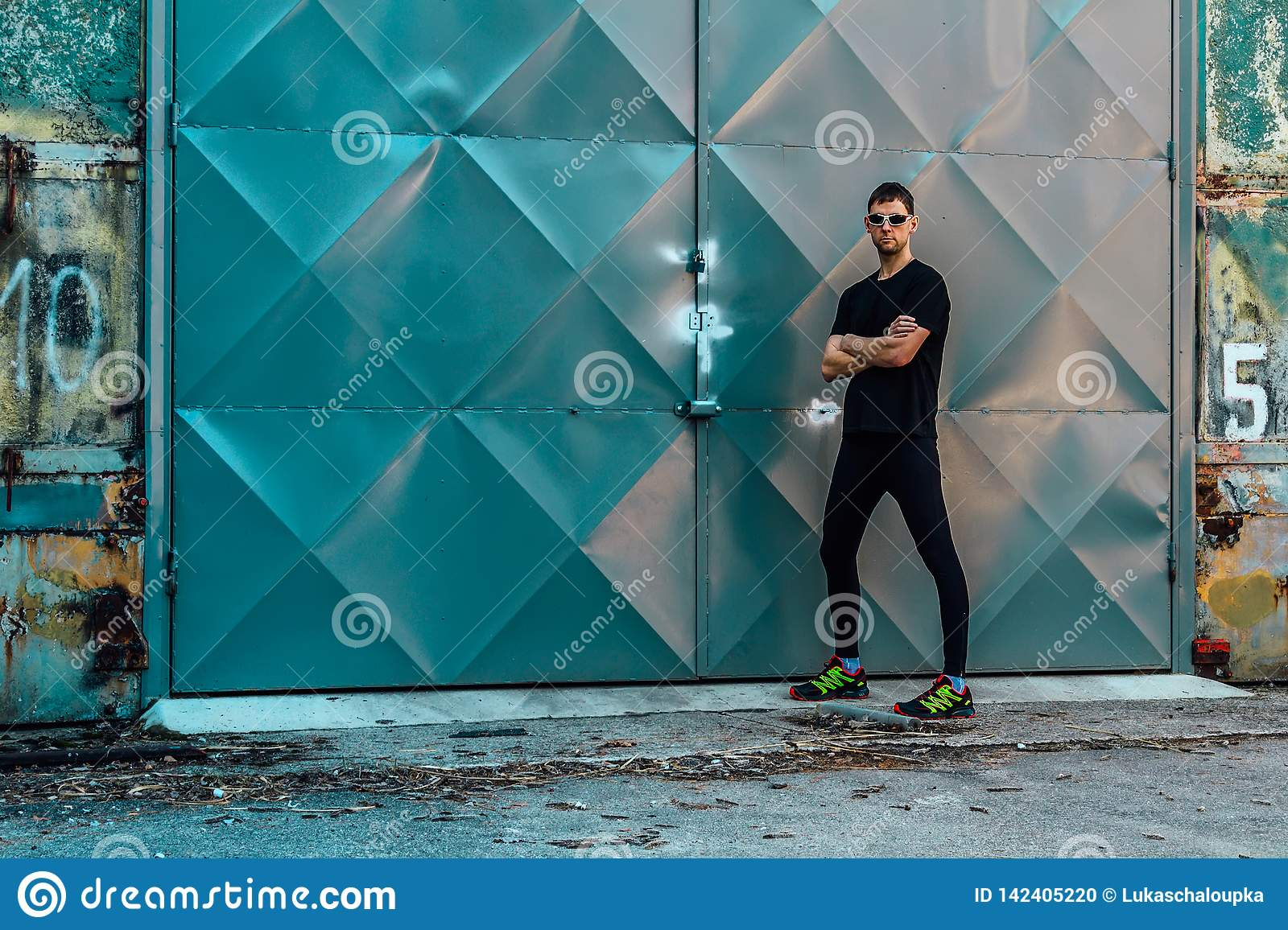 Handsome young man runner standing in front of door with sunglasses. Fitness, workout, sport, lifestyle concept